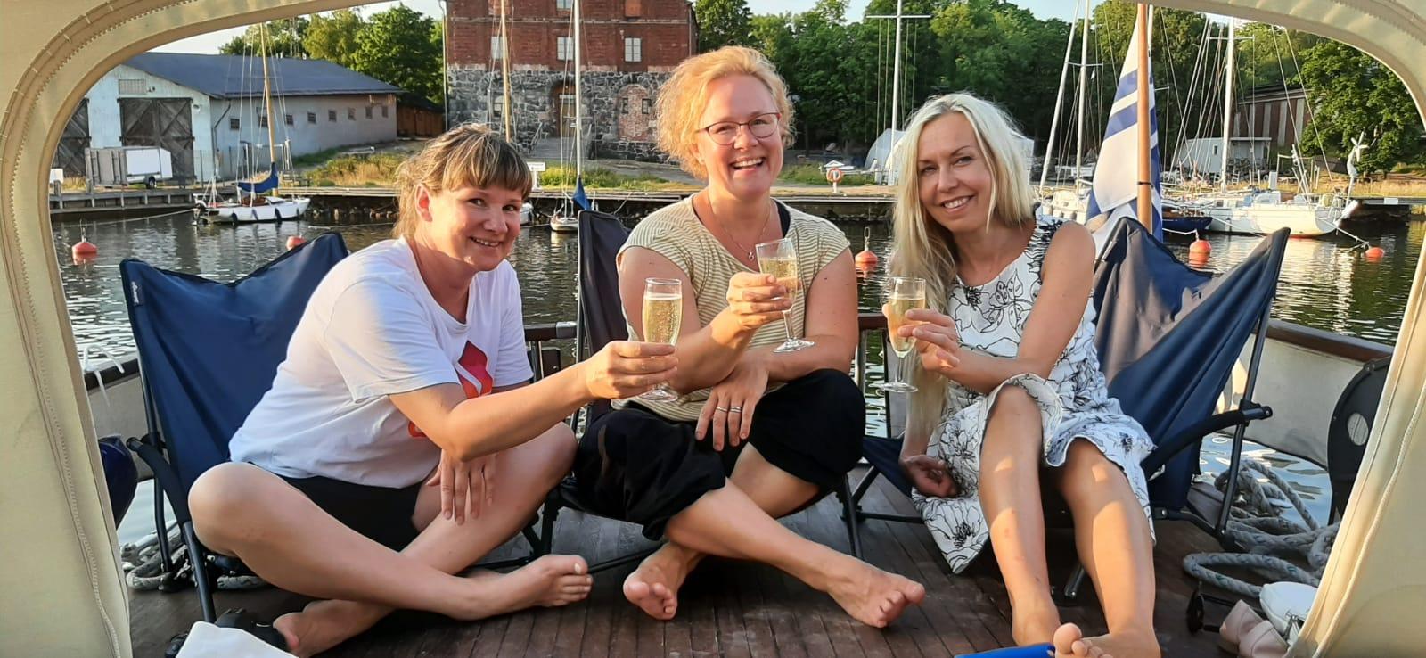 The Dream Team - Taru, Sanna & Päivi istuvat laivan kannella.