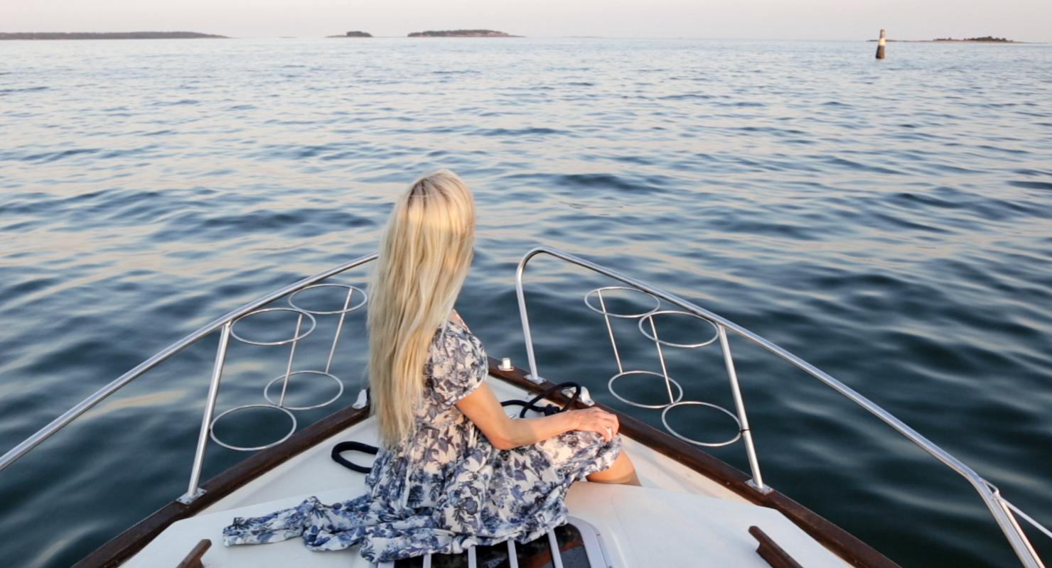 Päivi istuu veneen keulalla, edessä sinistä merta.